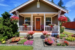 Cute American house exterior with covered porch and flower pots