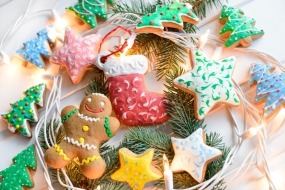 Christmas cookies with festive decoration and christmas lights on white wooden background. New Year and Christmas concept.