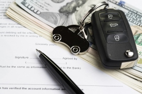 Buy or sell car, purchase or rent automobile service with key with car keychain on pile of US Dollar banknotes money on printed contract paper and pen to sign, finance installment or debt awareness